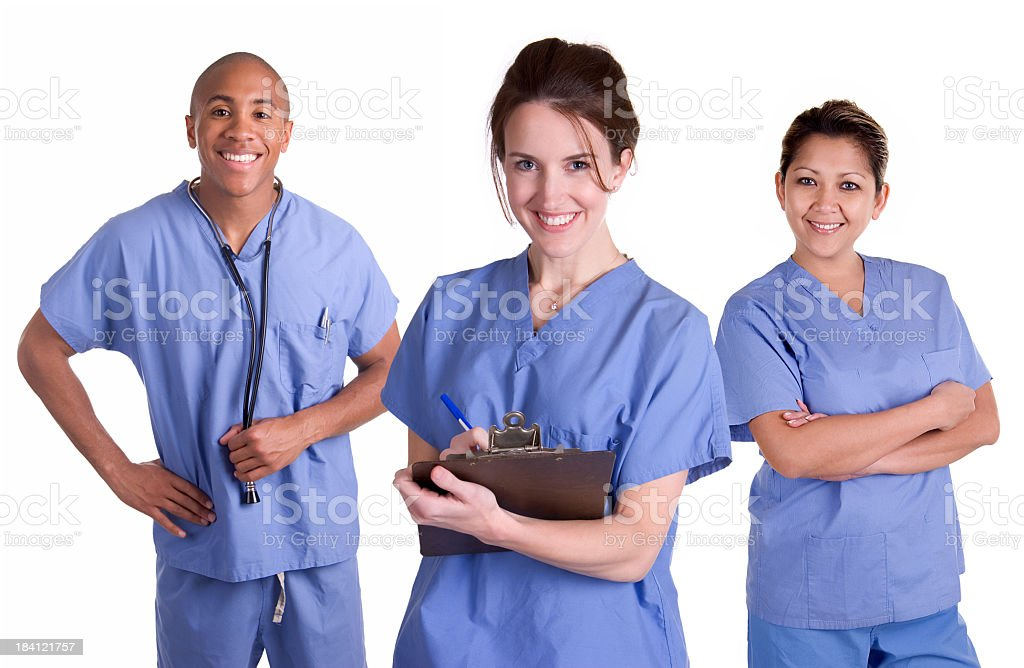 Three medical professionals in blue scrubs stock photo