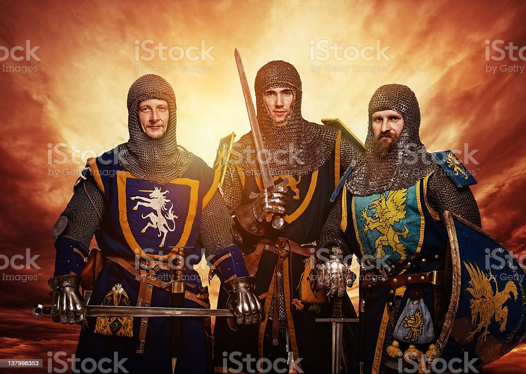 Three medieval knights against stormy sky. stock photo