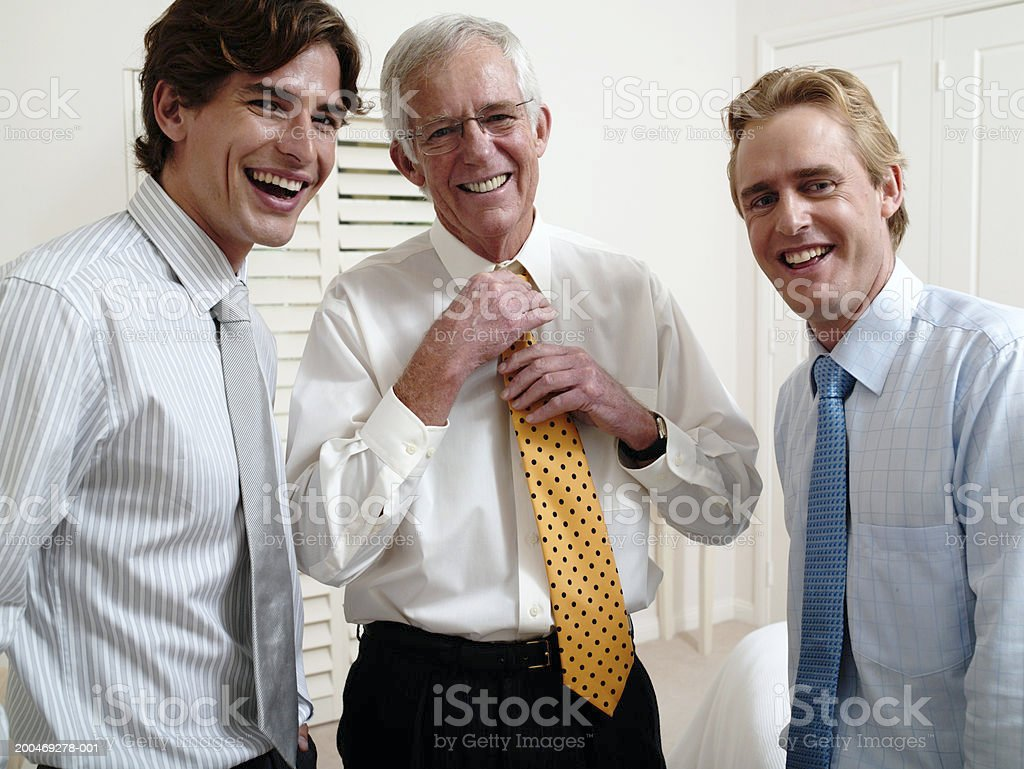 Three men adjusting ties, smiling, portrait royalty-free stock photo
