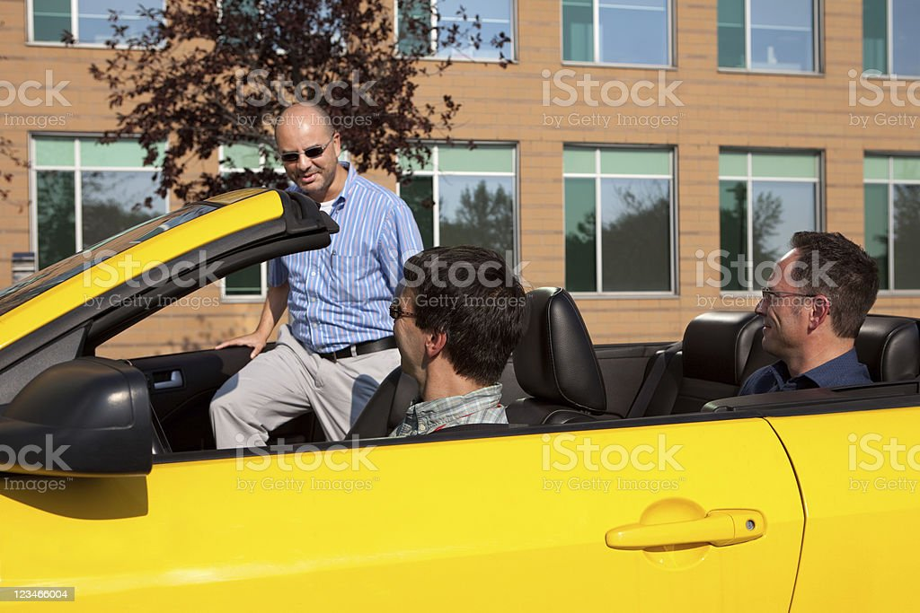 Three men car pooling in a yellow convertible stock photo