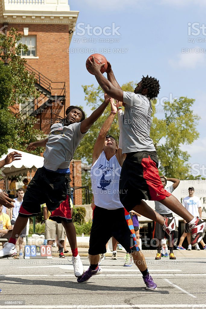 Three Men Fight For Rebound In Outdoor Street Basketball Tournament royalty-free stock photo