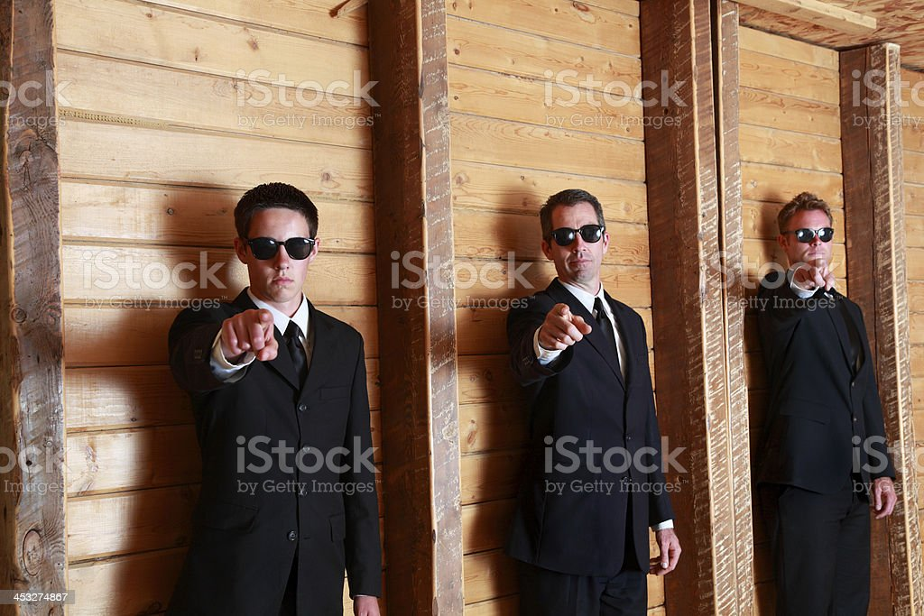 three men in black point at camera with danger menace royalty-free stock photo