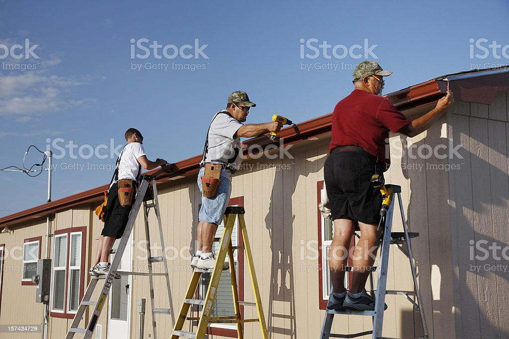 Three Men Installing Seamless Aluminum Gutters on Home stock photo