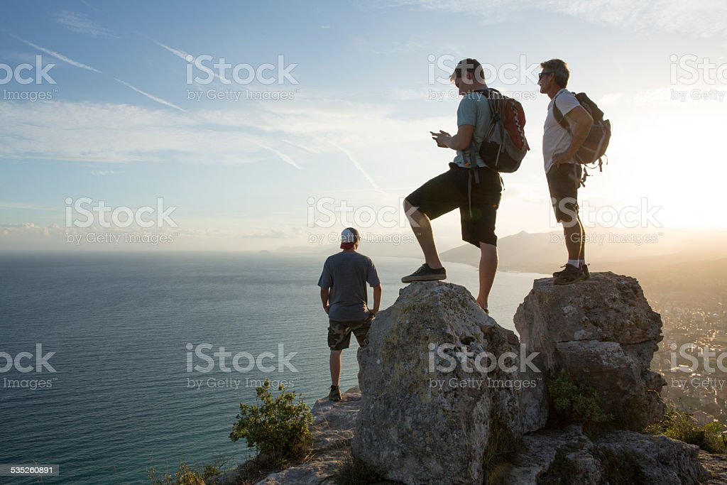 Three men look out to view at top of hike stock photo