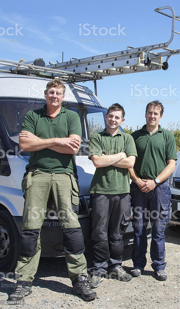 Three men on a building site preparing for work stock photo