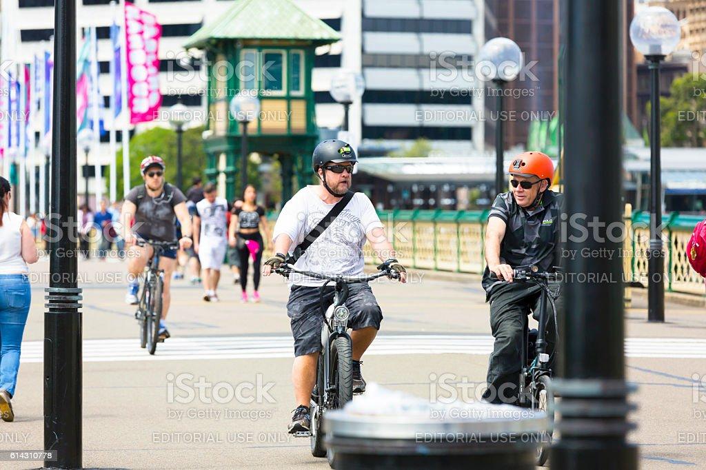 Three men rading bicycles on Pyrmont Bridge at Darling Harbour stock photo