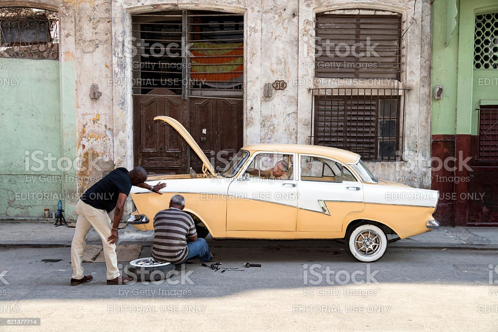 Three men restores old American car on Havana street, Cuba stock photo