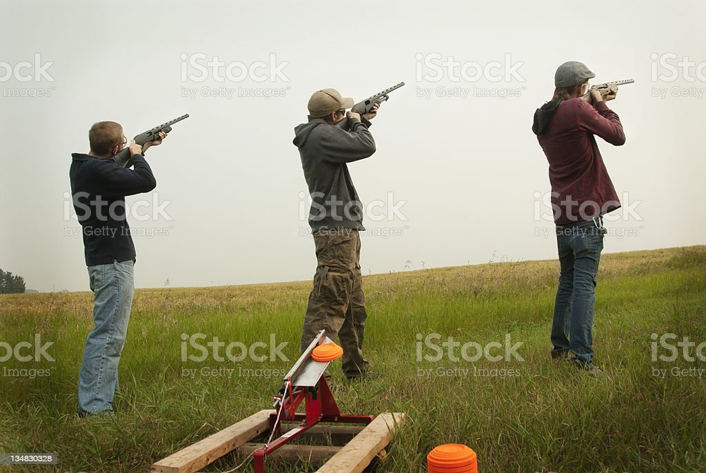 Three men shooting clay pigeons stock photo