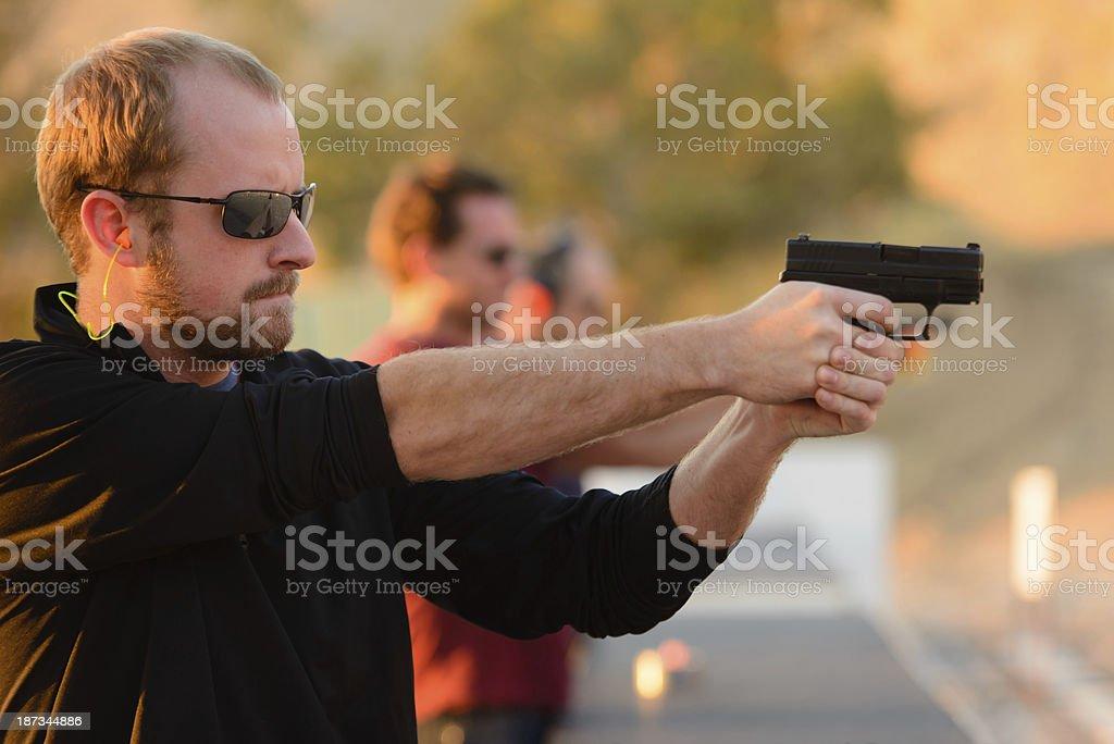 Three Men Shooting Handguns stock photo