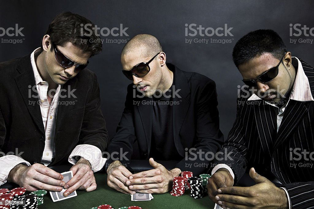 Three Men Sitting at Table Playing Poker and Checking Cards stock photo