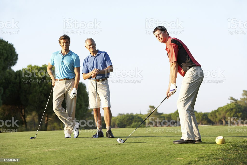 Three men teeing off on a golf course stock photo