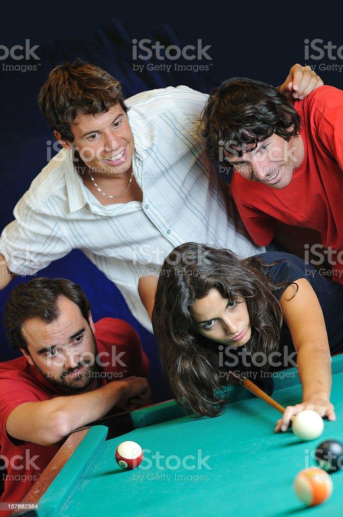 Three men watch woman shoot pool stock photo