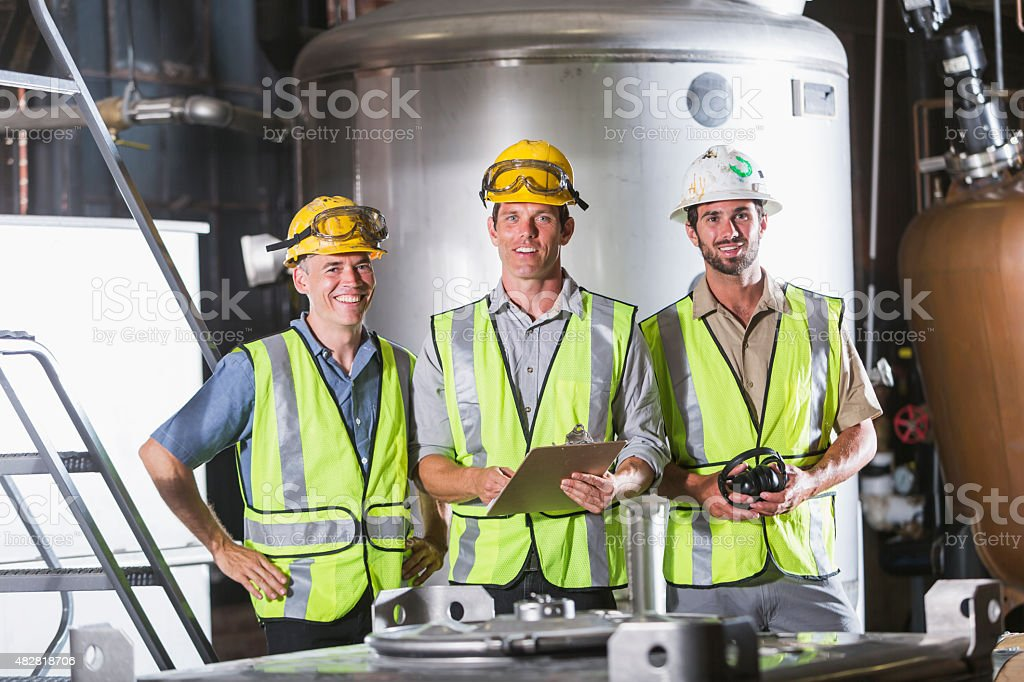 Three men wearing hardhats, vests and safety glasses stock photo