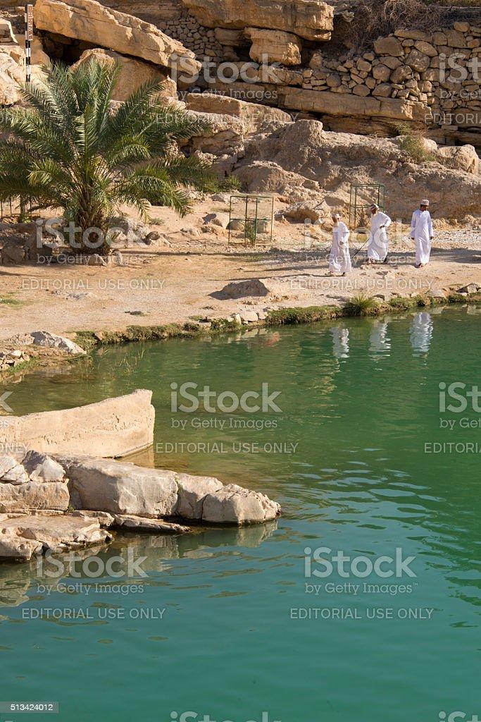 Three men wearing  traditional Omani costume walking in a wadi stock photo
