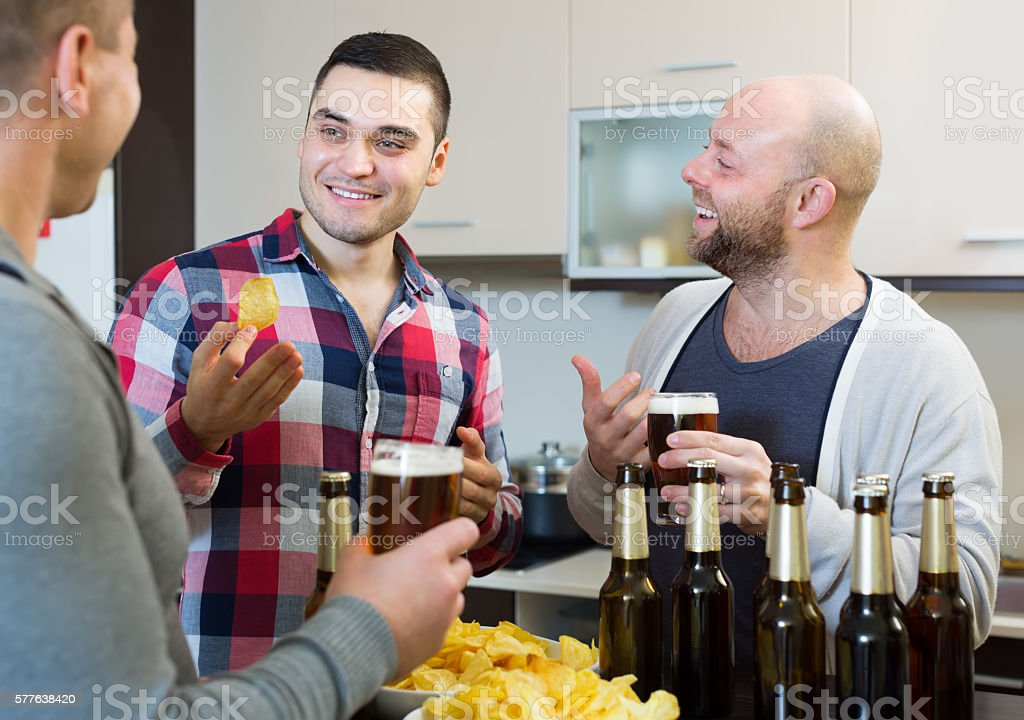 Three men with beer at kitchen stock photo