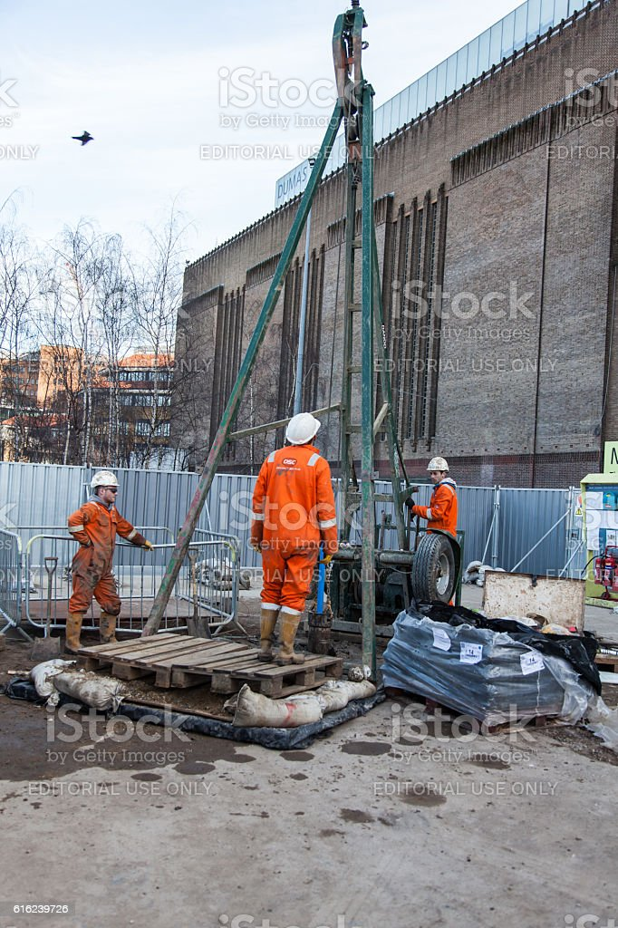 Three men work on a borehole drilling rig stock photo