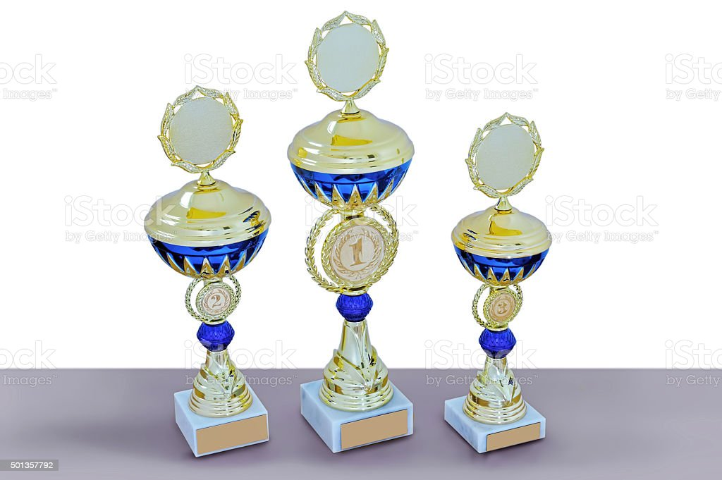 Three metal cups of gold color with blue details stock photo