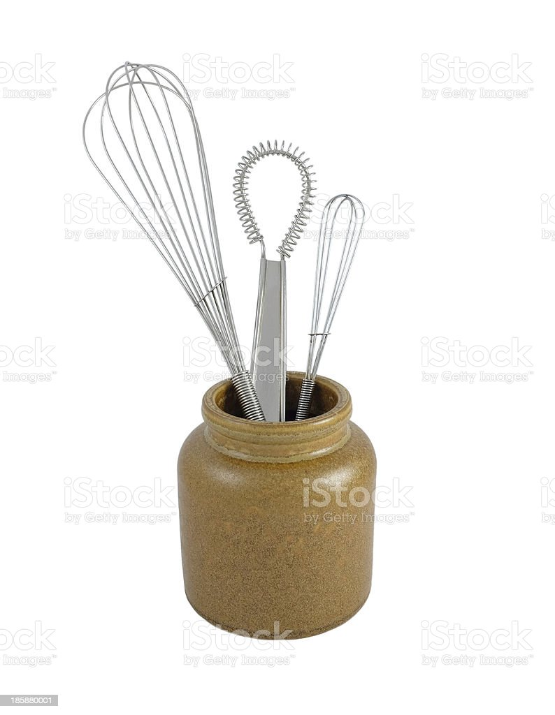 Three metal whisks in a brown ceramic jar stock photo