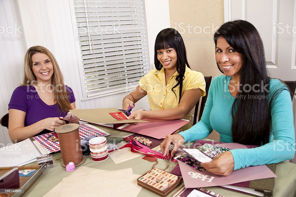 Three mid-adult friends. Group of multi-ethnic women scrapbooking. stock photo
