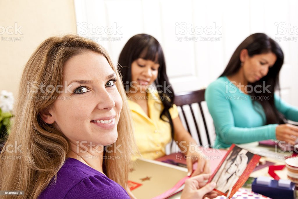 Three mid-adult multi-ethnic women friends scrapbooking. Art, craft, hobby. royalty-free stock photo
