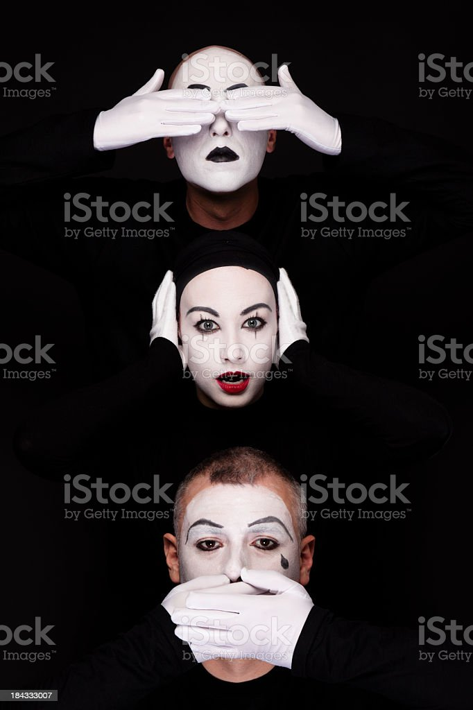 Three mimes heads depicting see hear speak no evil on black stock photo
