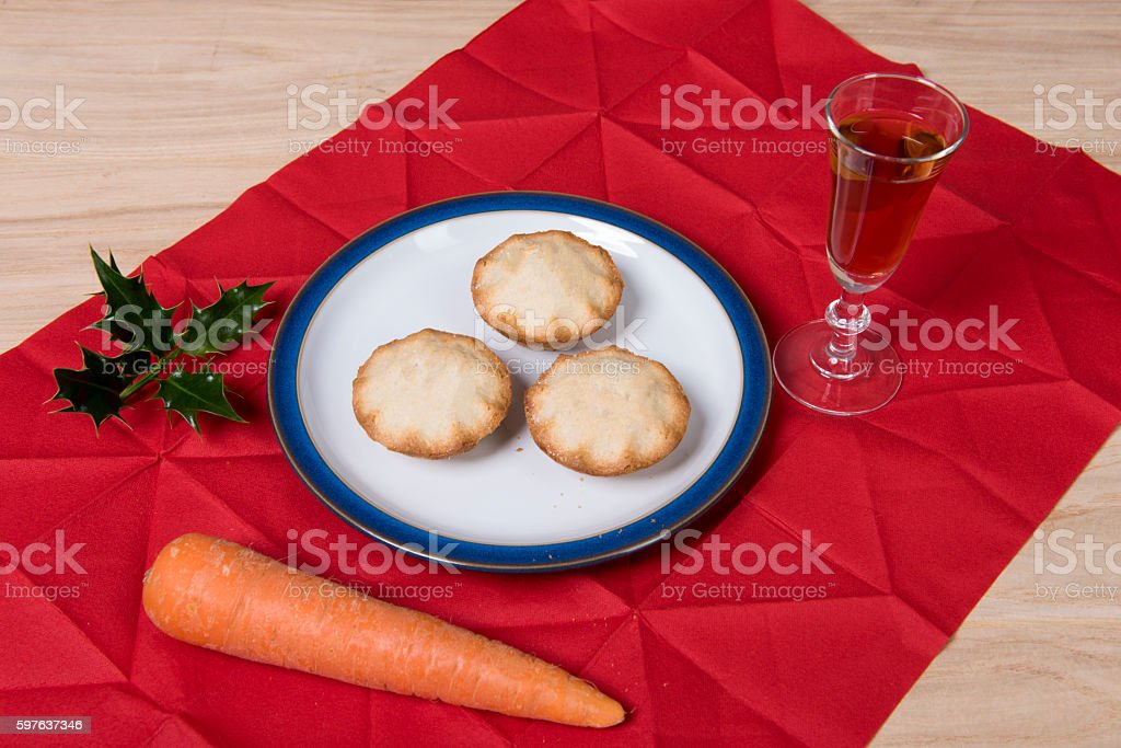 Three mince pies with sherry and a carrot stock photo