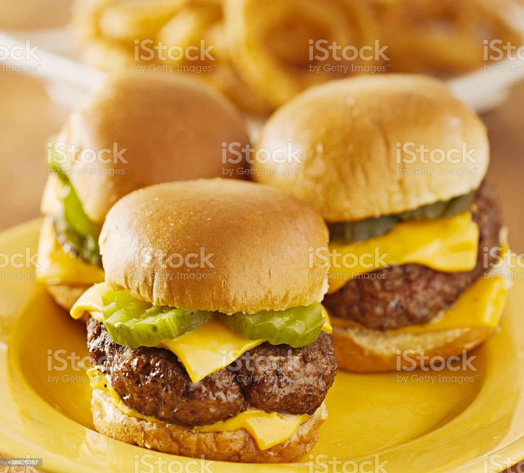 three mini burger sliders with cheese and pickles stock photo