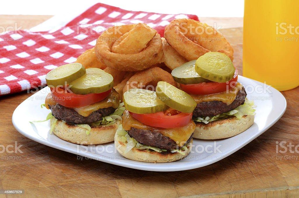 Three Mini Cheeseburger Sliders with Onion Rings stock photo