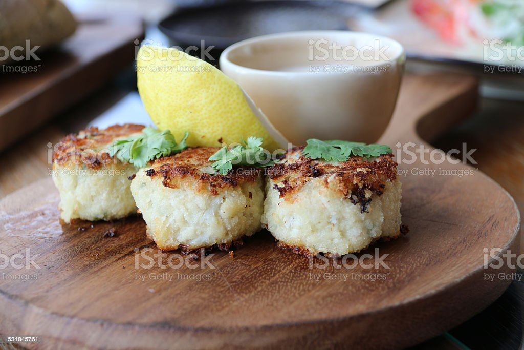 Three mini crab cakes with remoulade sauce and lemon wedge stock photo