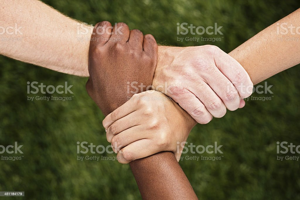Three mixed hands linked in unity stock photo