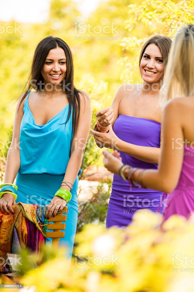 Three modern smiling young female friends outdoors stock photo