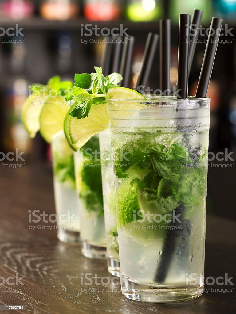 Three mojito cocktails in a row on a wooden bar stock photo