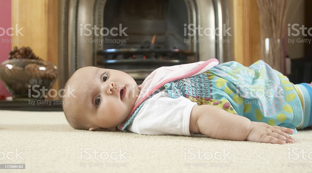Three month old girl lying on carpet royalty-free stock photo