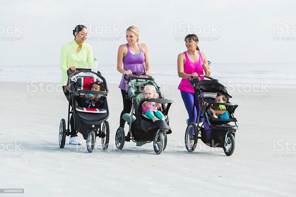 Three mothers and babies in strollers walking on beach stock photo