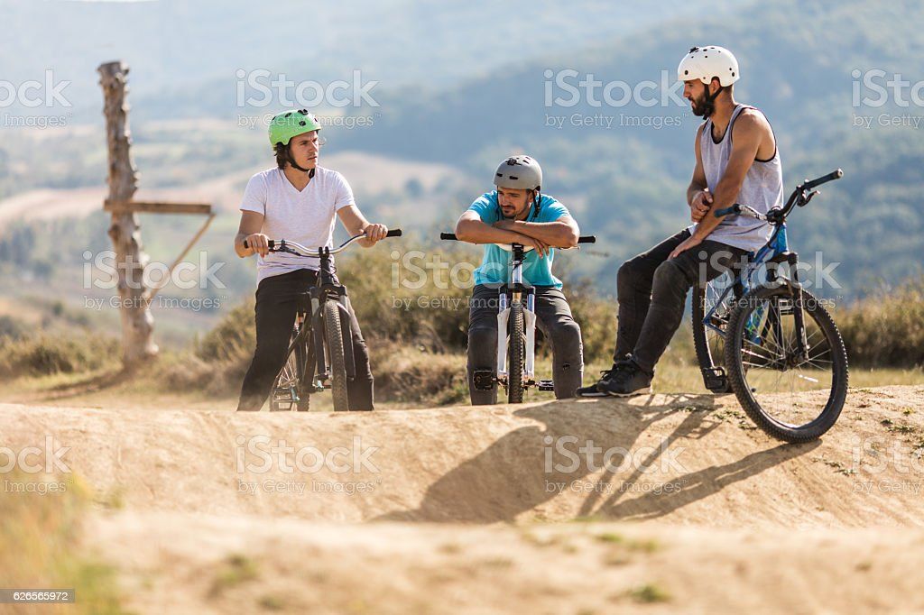 Three mountain bike cyclists relaxing on a dirt road. stock photo