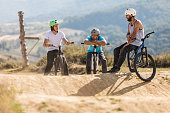 Three mountain bike cyclists relaxing on a dirt road.