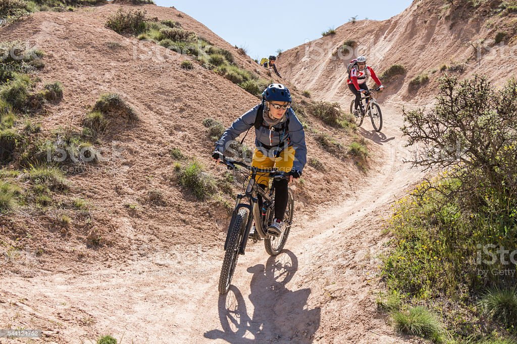 Three mountainbikers in Cappadocian S-shape curve, Turkey stock photo