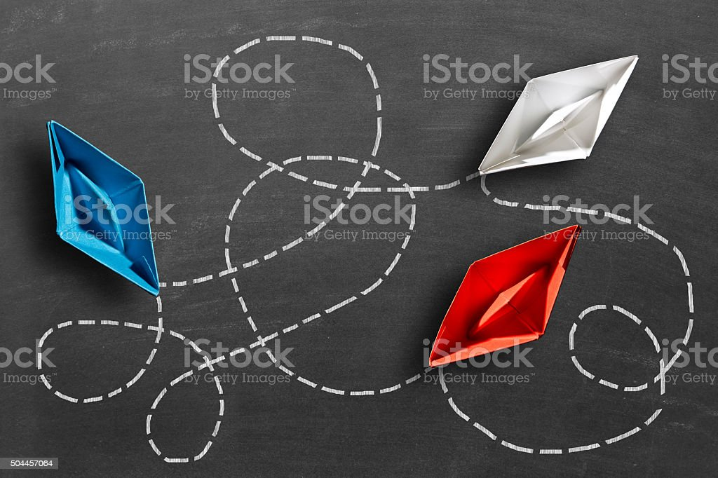 Three multi colored paper boats connected with dots stock photo