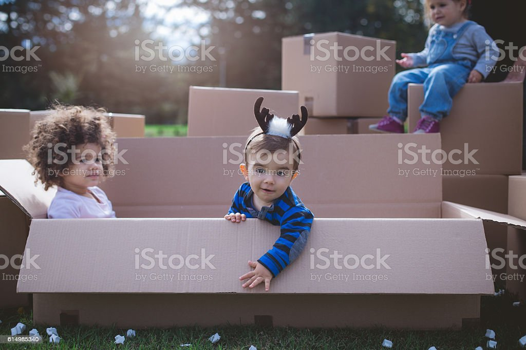 three multi ethnic babies playing - reindeer headband stock photo