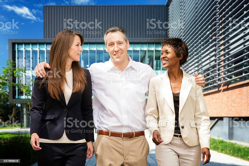 Three multi racial business people walk out of modern building stock photo