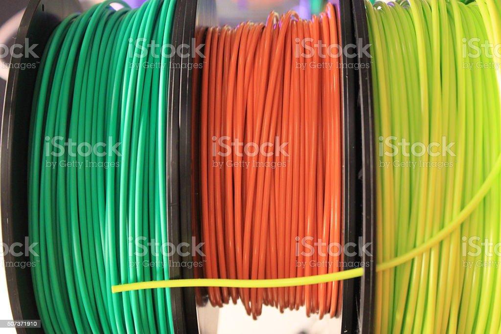 Three multi-color 3d printing filament spools stock photo