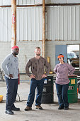 Three multi-ethnic blue collar workers in warehouse