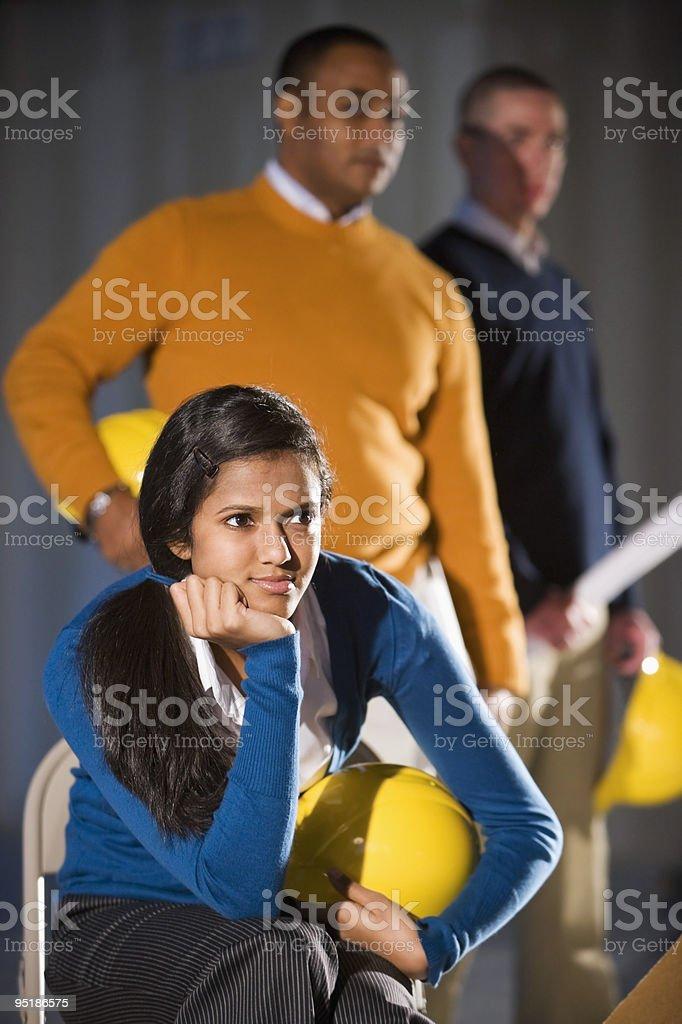 Tres multiétnico de gente de negocios sosteniendo cascos rígidos foto de stock libre de derechos
