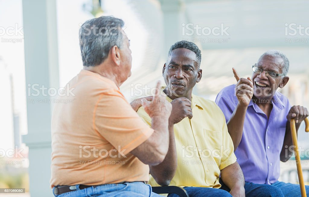 Three multi-ethnic senior men on bench arguing stock photo