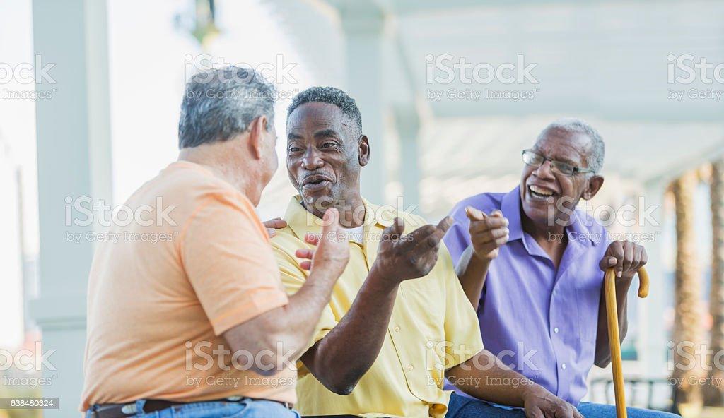 Three multi-ethnic senior men on bench talking stock photo