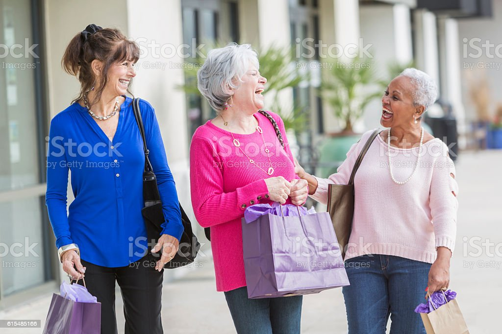 Three multi-ethnic senior women out shopping stock photo