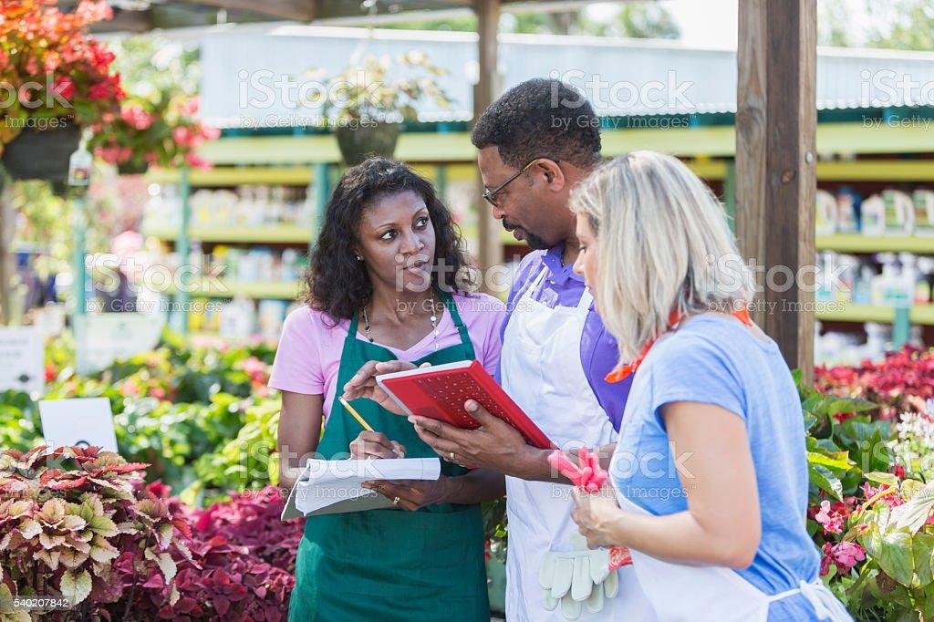 Three multi-ethnic workers in garden center stock photo