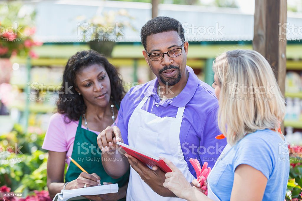 Three multi-ethnic workers in garden center stock photo