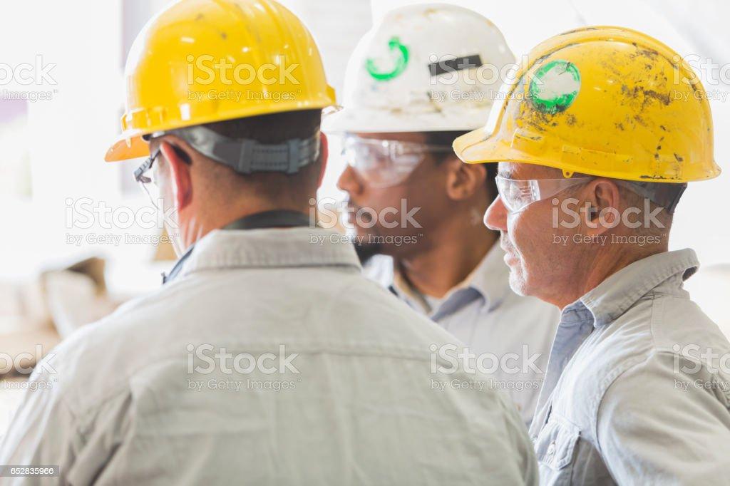 Three multi-ethnic workers in hardhats having meeting stock photo