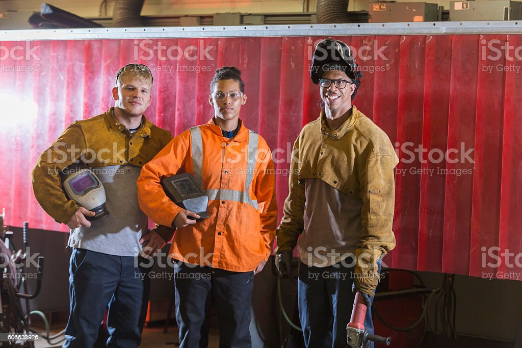 Three multi-ethnic workers with welding equipment stock photo